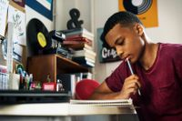 Teenager writing at his desk in his bedroom