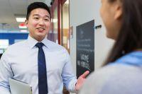 Principal speaking with teacher in school hallway
