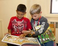 Two elementary school students reading books together