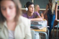 Student wearing headphones listening to music in a classroom