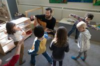 Elementary school teacher playing guitar while children dance around