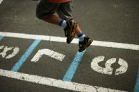 Elementary school student playing hopscotch