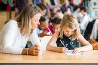 Teacher sitting with elementary student while she writes in a notebook