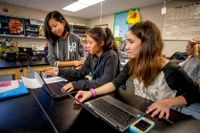 Students using laptops in science class