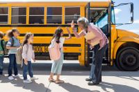 Elementary school principal high fives students as they board their school bus
