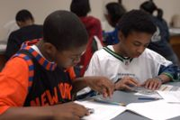Two students using a calculator to complete math problems