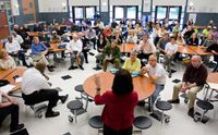 Administrator meeting with staff in a cafeteria