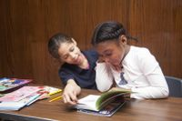 Two elementary school students reading a book together