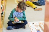 Elementary student sitting on the floor and working independently