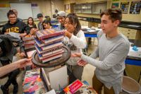 high school students stack books in a physics class