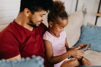 Young family online learning together on a portable computer.