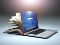 A computer and book indicating new challenges in digital learning.