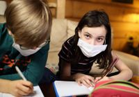 Children doing homework at home in masks during quarantine covid-19