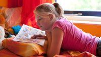 Teenage girl reading a comic book in her bedroom