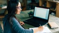 Woman writing in notebook in front of laptop at home