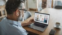 Man has video conference with several people at home