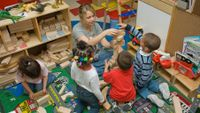 Teacher and pre-k children in classroom play with blocks.