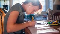 Teenager writing at her kitchen table