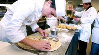 Young man prepares food in restaurant kitchen