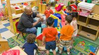 Preschool teacher playing with building blocks with a group of students