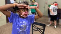 An elementary school student wears a mask during a drama camp activity