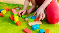 Child plays with wooden blocks on floor