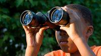 Boy looking through binoculars outside.