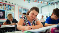 Middle school girl writing in classroom