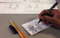 An over the shoulder view of a student drawing comics