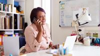 Woman at home speaking on phone sitting at desk with laptop