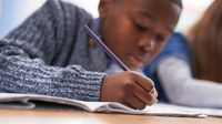 Elementary aged boy at school writing at desk