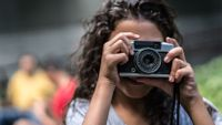 Young girl using a vintage camera to take photos