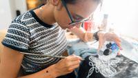 Teenage girl painting fabric