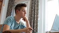 Boy doing homework at home on laptop