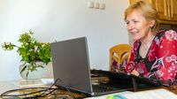 Woman using her laptop at her kitchen table