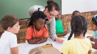 Elementary school teacher helps students in classroom