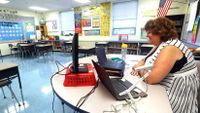 Teacher instructing students remotely sitting at her desk in her classroom