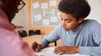 Teacher helps high school student work on project