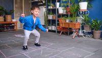 Preschool-aged boy playing hopscotch at home
