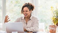 Woman gesturing while working at her laptop at home