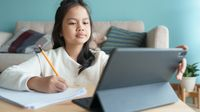 Elementary-aged girl writing in a notebook while working on her tablet during distance learning