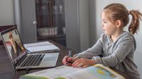 Elementary aged girl participates in distance learning at home