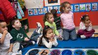 Pre-school children sitting on rug in classroom