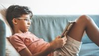 Middle school aged boy reading book on couch at home