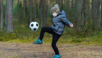 Boy kicking a soccer ball outside while wearing a mask