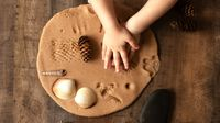 Child's hands pushing objects from nature into clay