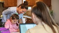 Mother helping her daughters during distance learning classes