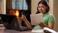 Teenage girl completing school work on her laptop