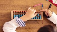 Elementary aged girl using abacus for math