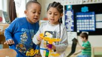 Two kindergartners working on a marble project in class